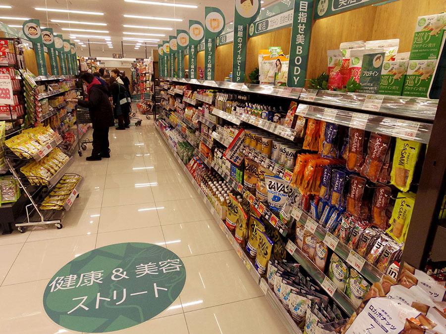 ▲ 核店舗のSMでは、イズミヤで初めて「健康&美容ストリート」コーナーを導入。「健康」「美容」を軸に、加工食品や日配など部門の枠を超えて商品を揃える
