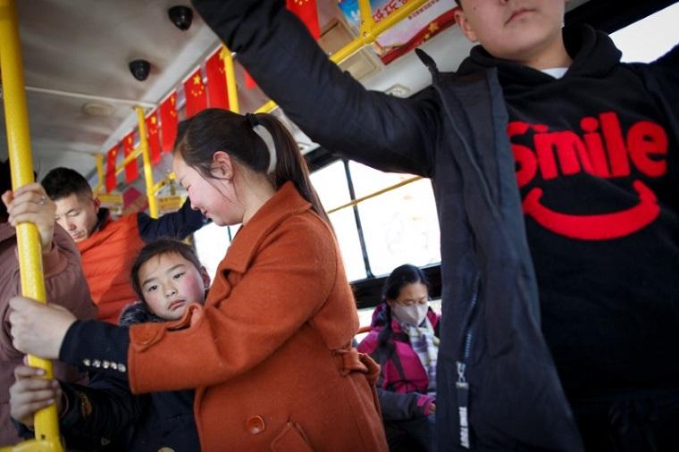 河南省洛陽市でバスに乗る人々