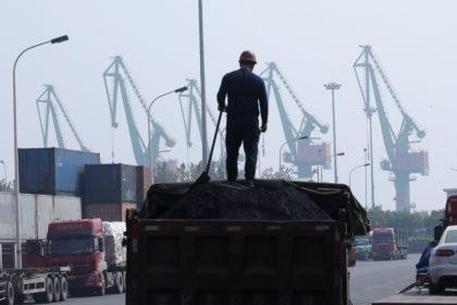 天津港近くの物流施設で石炭を積み込む労働者。