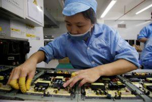 TV工場の生産ラインで働く従業員