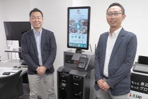 株式会社日本システムプロジェクト専務取締役の毛受義明氏(左)、 「Pay Cube」を採用した同社の外食向けセルフレジ(中央)、 株式会社日本コンラックス特機営業本部企画推進部部長の吉田真一氏(右)