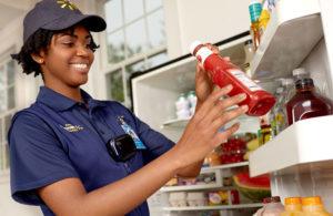 配達員が冷蔵庫に商品を補充している様子