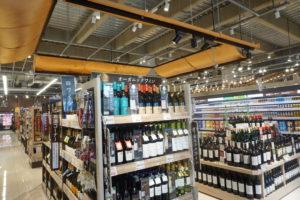 酒類売場ではオレンジ色のテントを採用。ワインの棚には木目調にしてナチュラルな雰囲気を醸し出す