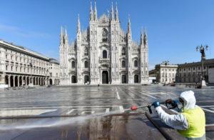 イタリア ミラノのドゥオーモ前で消毒をする人