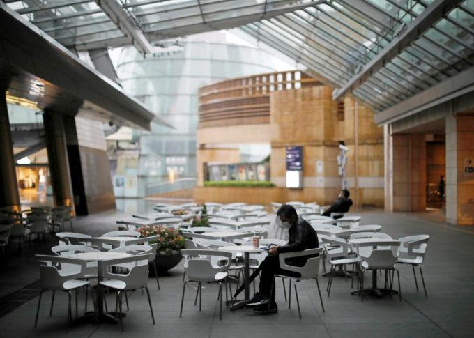 都内で人のほとんどいないカフェに座る人
