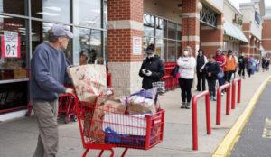スーパーに入るため行列する人々