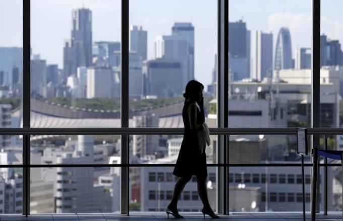 東京都内のオフィスビル内を歩く人