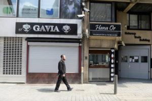 ベルギーでシャッターの閉まった店の前を歩く人