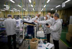 写真は製造した人工呼吸器のチェックをするメトランの従業員