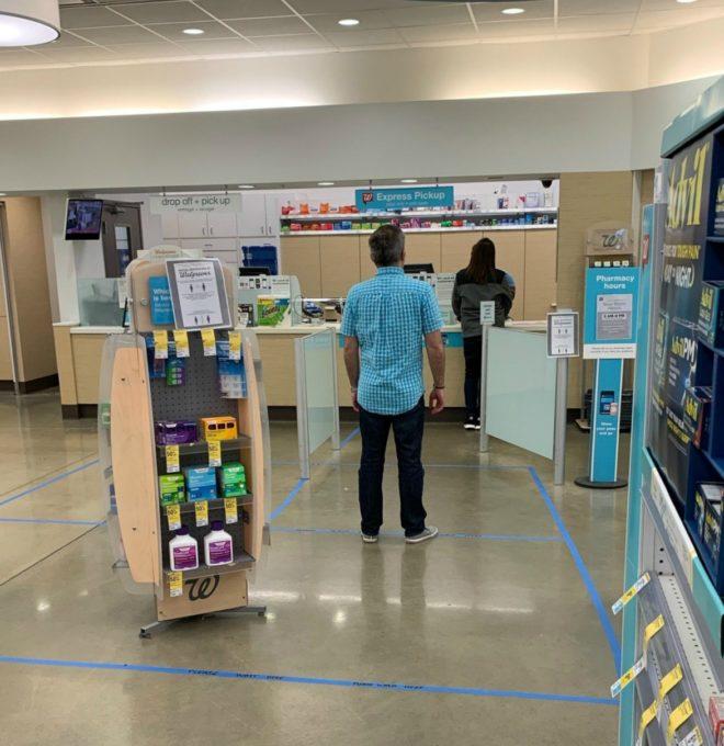 ウォルグリーンの薬局でソーシャルディスタンスを保って待機している来店客