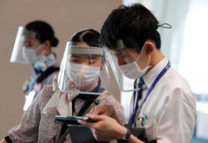 羽田空港でフェイスシールドなどを着けて乗客を案内する全日空の従業員