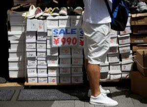 セールの広告が張られた靴売り場を見ている男性客