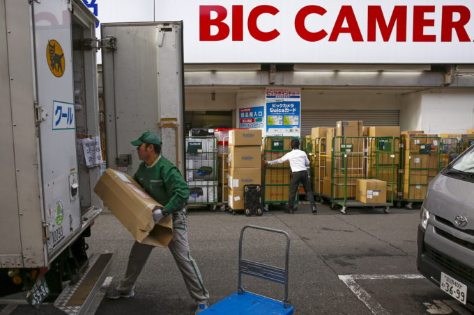 ビックカメラ店舗の外で荷物をトラックに積む配達業者