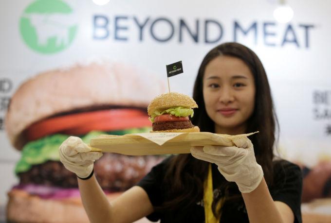 ビヨンド・ミートが製造した植物由来のパテを添えたバーガーを展示するスタッフ