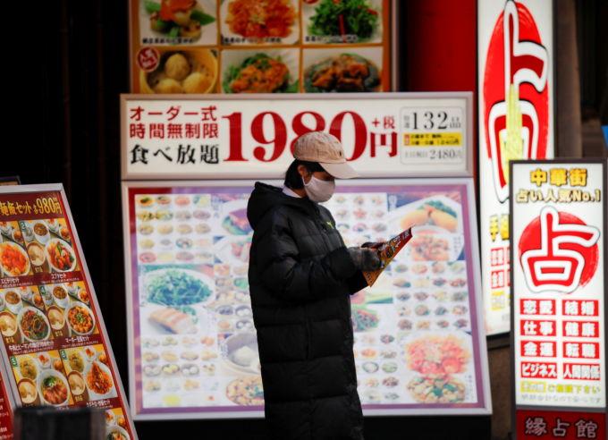 横浜の中華街でマスク着用で店頭に立つレストランの従業員