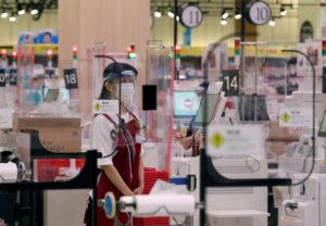 マスクとフェースシールドをつけて買い物客に対応するスーパーの従業員