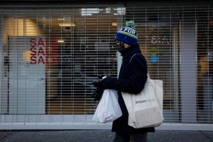 米ニューヨークでシャッターが閉まる店舗前を歩く人