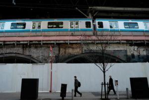 都内の駅に停まっている電車と線路沿いを歩く人