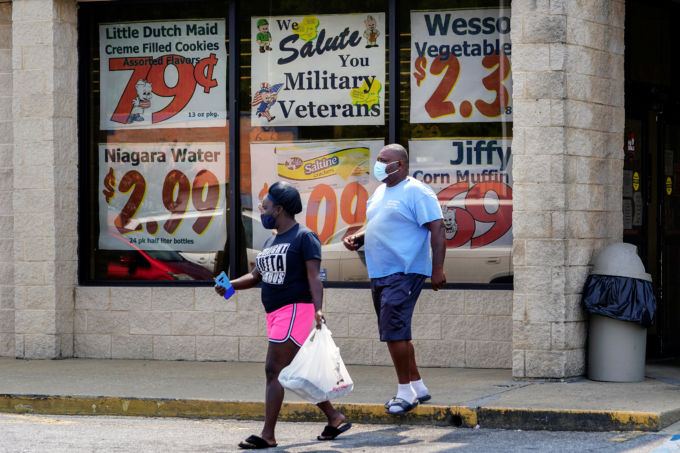 ジョージア州コロンバスでマスクを付けて歩く人