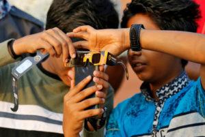 インドのケララ州の店舗で携帯電話を操作する人