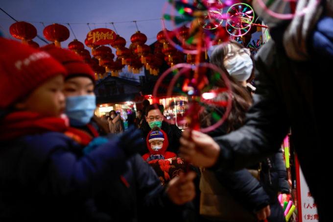 春節の飾りつけがされた北京で買い物をする人
