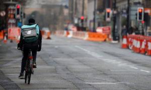 英マンチェスターの中心市を走るデリバルーの配達員