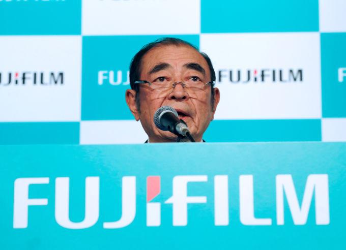 富士フイルムホールディングス古森重隆会長兼最高経営責任者と同社のロゴ