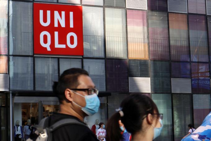 ユニクロのロゴマークが見える建物の前を通行するマスク着用の男性