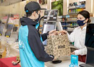 ローソンの従業員から商品を受け取る「ウォルト」配達員