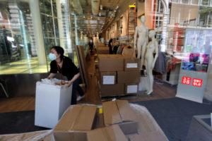 NYマンハッタンのユニクロの店内で梱包された商品を移動させている従業員
