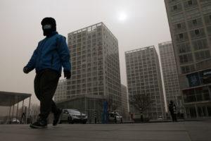 北京を歩くマスク姿の配達員