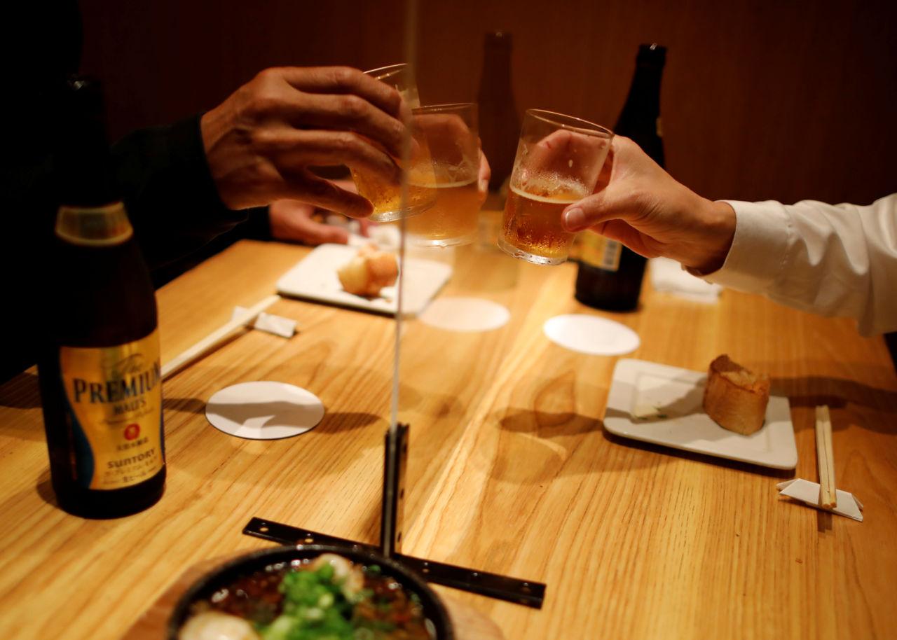 居酒屋でアクリル板越しに乾杯をするようす