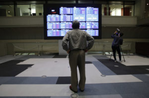 東京証券取引所で株価ボードを見る人