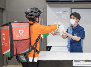 ローソンの従業員から商品を受け取るDiDiの配達員