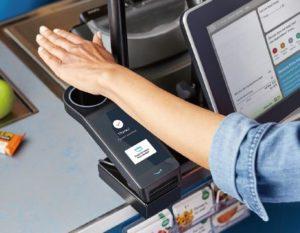 「アマゾン・ワン」の専用端末で手のひらをかざして決済する様子