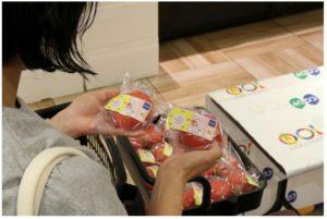 「見える化」されたトマトを手に取る人