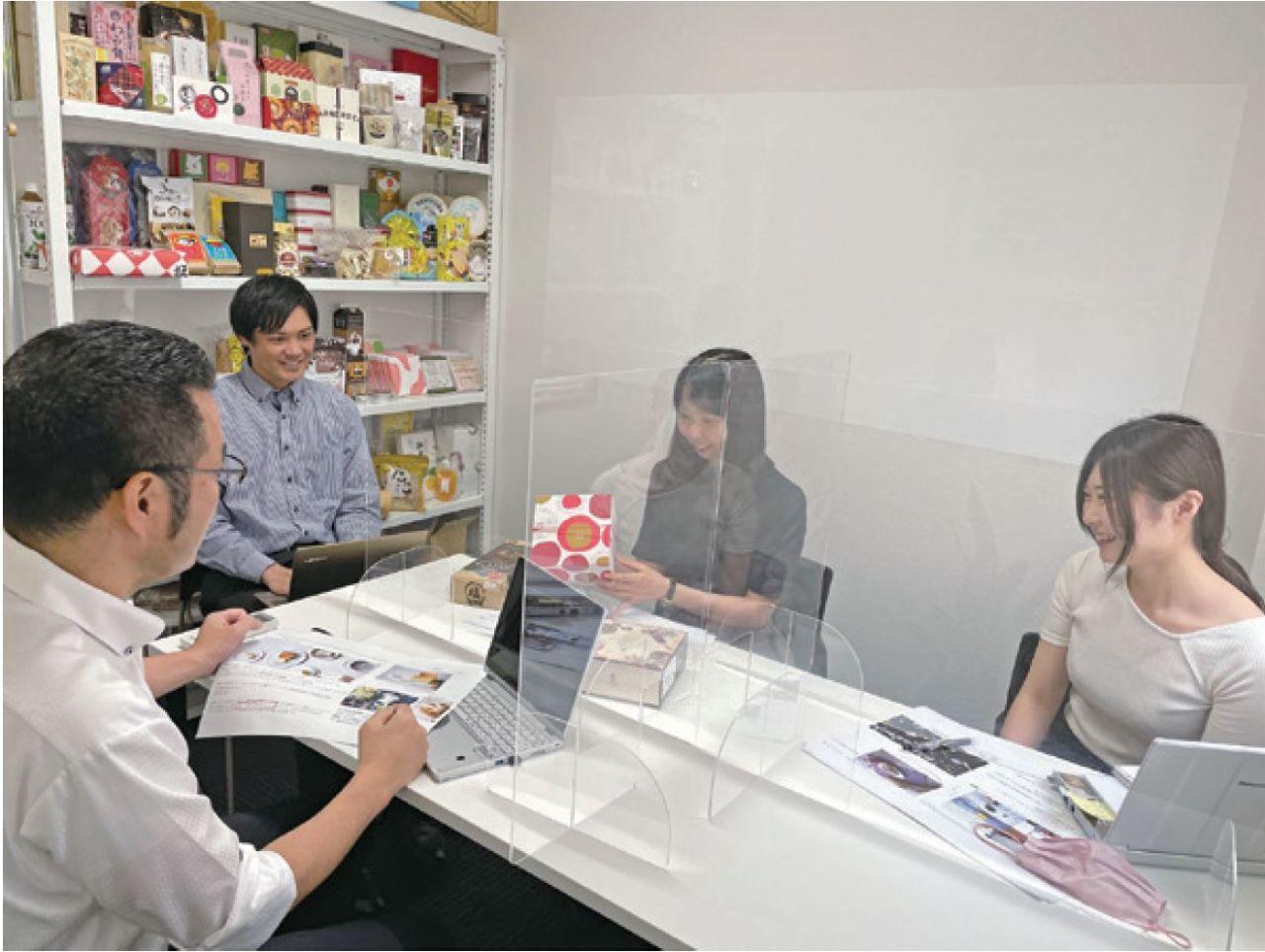 トップ食品の従業員が収集した商品を吟味するミーティング風景